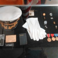 Military hat, gloves, and medals.