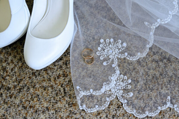 White shoes with heels and gold wedding rings on white lace veil.
