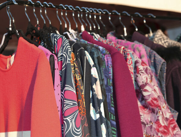 Many vintage style clothes and retro for sale at an outdoor flea market
