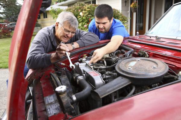 Senior man and son working on car engine