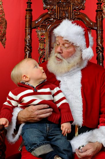 Baby boy sitting on Santa's lap at Christmas time.